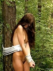 Teen babe tied up to a tree in the forest